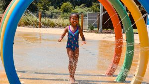 child running through water rings in zero depth splash park