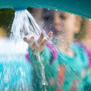 toddler playing at water park splash pad